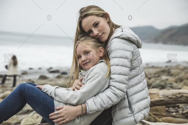 Portrait of confident teenage girl with sister sitting on shore at beach