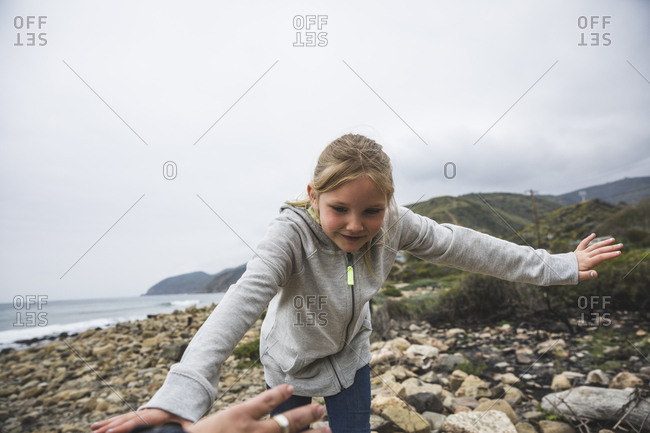 Little girl with arms outstretched standing on rocky shore at beach