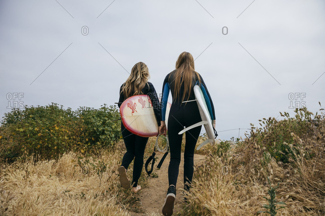 Rear view of mother and daughter in wetsuits carrying surfboards while walking toward beach