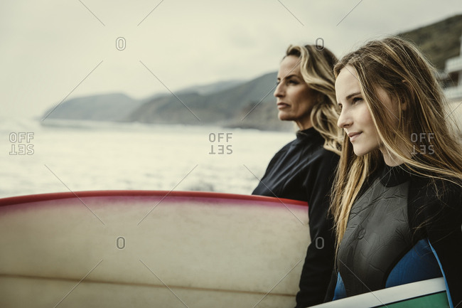 Confident mother and daughter carrying surfboards while looking at sea