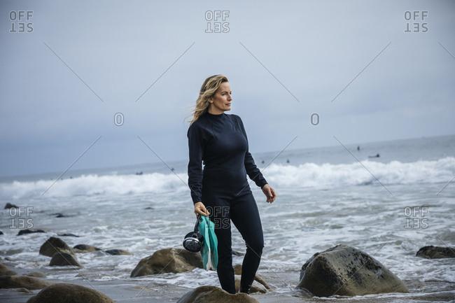 Mature woman holding snorkel gear at beach