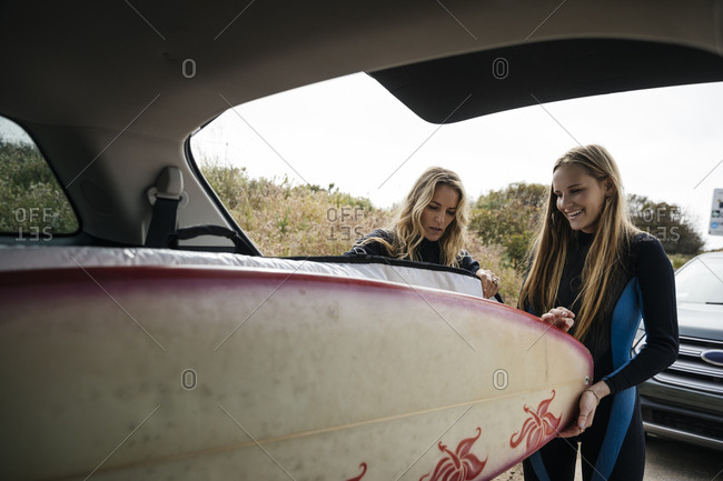 Happy mother and daughter loading surfboards in car trunk