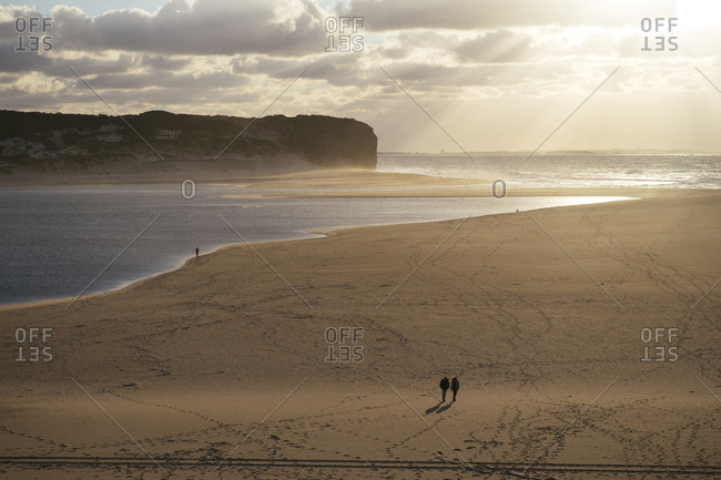 Two people walking and a fisherman on a solitary beach in Central Portugal