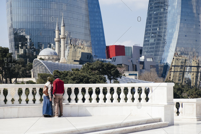A Muslim couple stand in Dagustu park, Baku, Azerbaijan, Looking at the Sehidliq Mosque and the Flame Towers