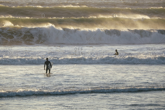 Two surfers waiting to catch waves