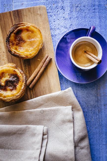 Pastel de nata and espresso coffee with two cinnamon sticks