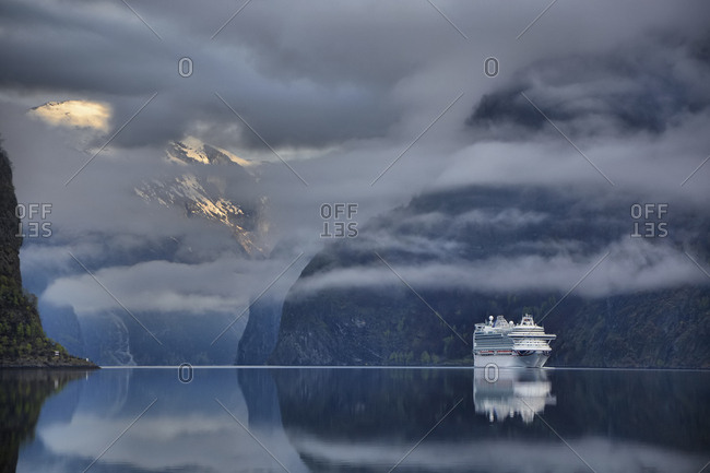Reflection of ship on a calm lake, surrounded by mountains.