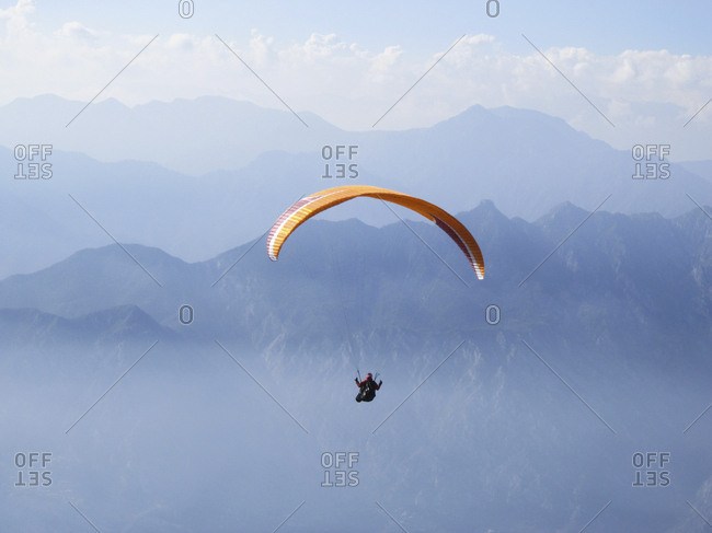 Person skydiving with orange parachute with mountains and clouds in the distance.