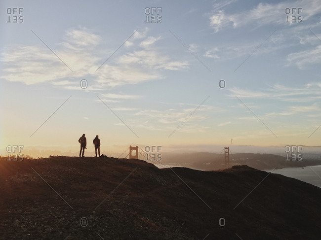 Silhouette of two people standing on a hill overlooking San Francisco Bay, with the Golden Gate Bridge in the distance. Sunset.