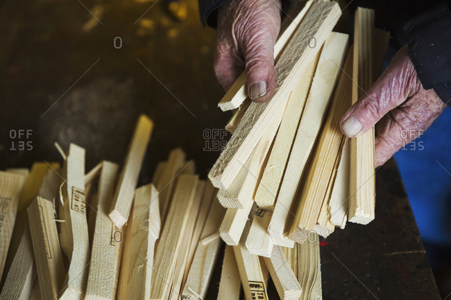Close up of a man in a sailmaker's workshop holding a bundle of wooden pegs.