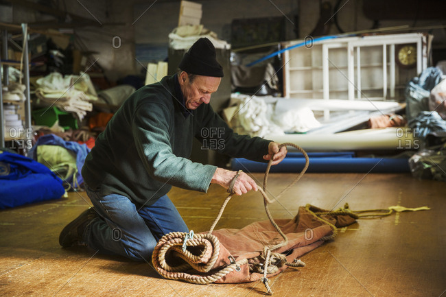 Man in a sailmaker's workshop kneeling on the floor, tying a rope on a sail.