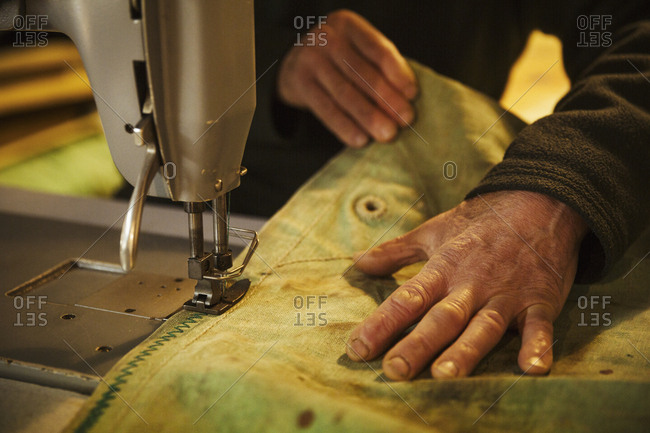 Close up of a man in a sailmaker's workshop sewing a sail with a sewing machine.