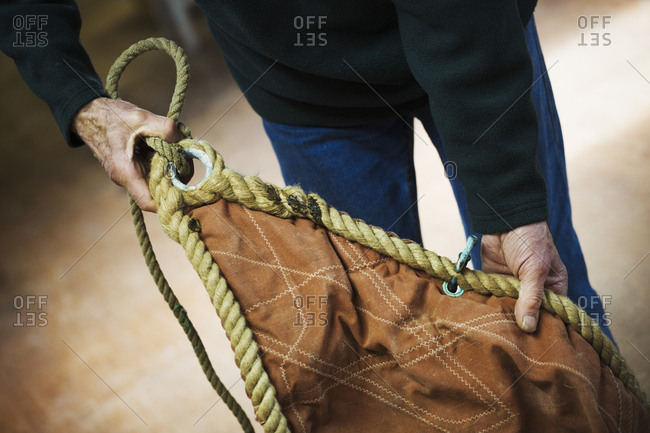 Close up of a man in a sailmaker's workshop holding a sail.
