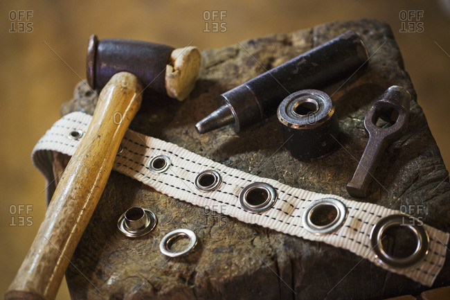 Close up of tools and eyelets in a sailmaker's workshop.