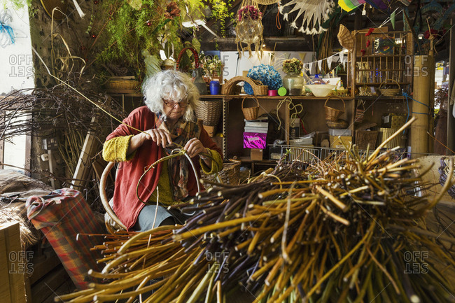 Woman weaving a basket in a weaver's workshop, bundles of willow.