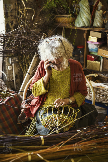 Woman weaving a basket in a weaver's workshop.