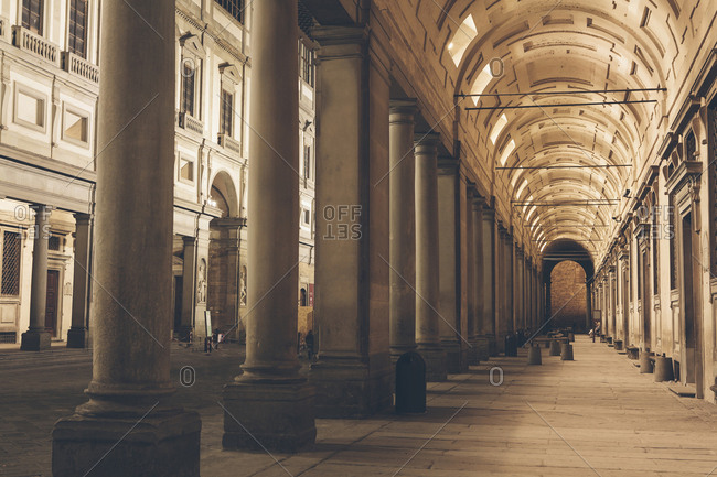 The Palazzo Vecchio and  Uffizi Gallery, historic building and colonnade reaching into the distance, at night.