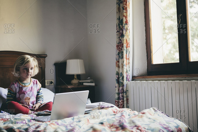 A three year old girl sitting on a bed in a hotel room, looking at a laptop computer screen intently,.
