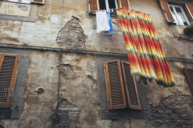 Laundry hanging from washing lines high above the street in Cortona, historic city in Tuscany,