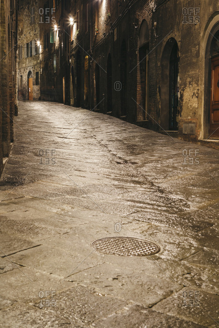 A deserted narrow street in the city of Siena at night