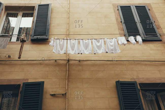Laundry hanging from washing lines high above the street in Siena historic city in Tuscany,