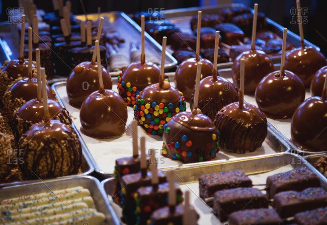 Display of caramel dipped apples and other candies on a stick