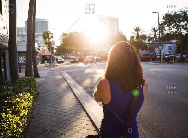 Back of woman walking on sidewalk in Fort Lauderdale, Florida