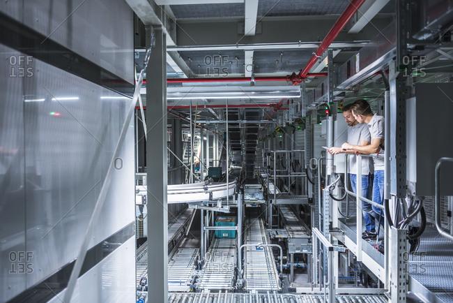 Two men talking in automatized high rack warehouse