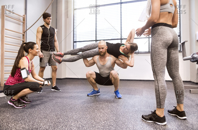 Young people doing fitness training in gym- lifting partners