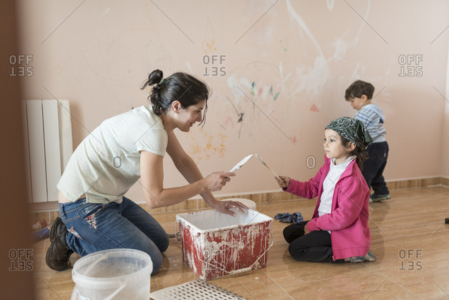 Mother and children painting wall in children's room
