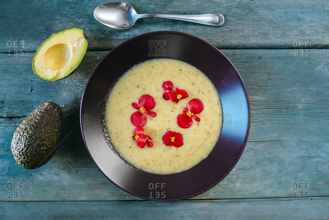 Cream of avocado soup garnished with edible flowers
