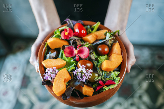 Man's hands holding bowl of mixed salad garnished with edible flowers- close-up