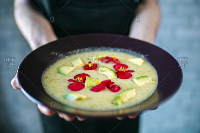 Man's hands holding cream of pumpkin soup garnished with edible flowers- close-up
