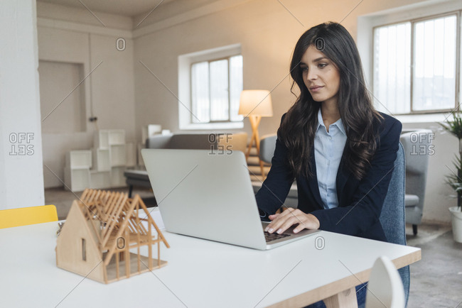 Young businesswoman using laptop on table next to architectural model