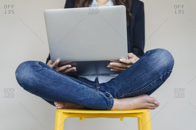 Barefeet businesswoman sitting on chair using laptop