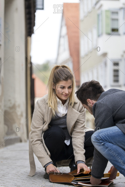 Young man collecting documents of young woman on the street
