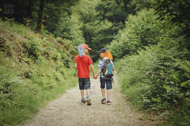 Two boys walking hand in hand with dip nets