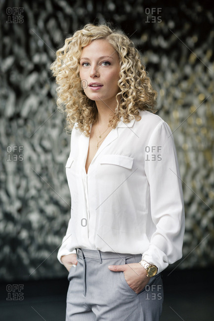 Portrait of blond businesswoman with hands in pockets