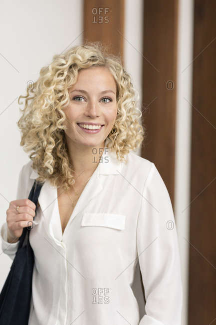 Portrait of smiling blond businesswoman with shoulder bag