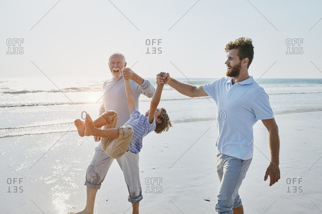 Happy grandfather- father and son on the beach