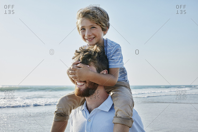 Father carrying son piggyback on the beach- son covering father's eyes