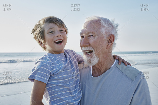 Happy grandfather carrying grandson on the beach