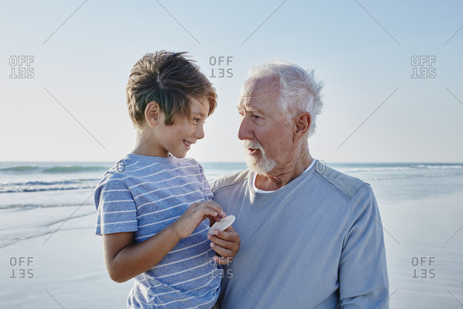 Grandfather with grandson on the beach