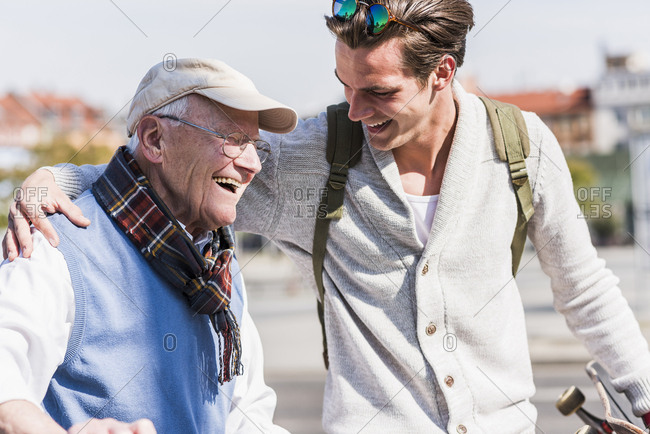 Happy senior man with adult grandson in the city