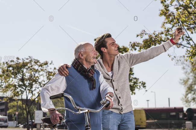 Senior man and adult grandson taking a selfie outdoors