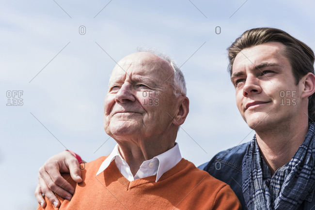 Smiling senior man and adult grandson outdoors