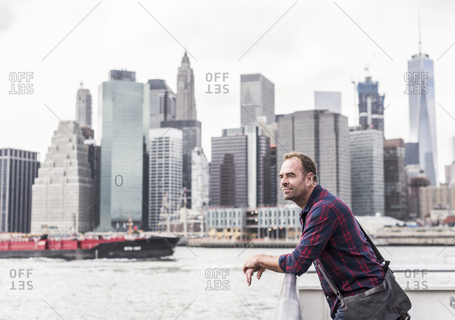 USA- New York City- man on ferry with Manhattan skyline in background