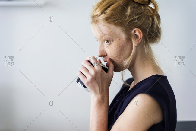 Young woman standing in kitchen- drinking coffee