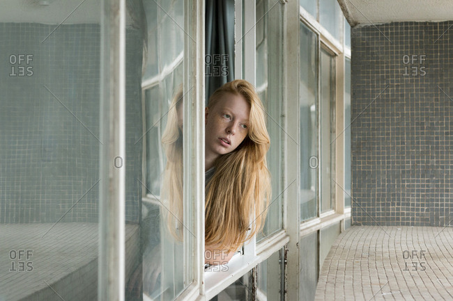 Ginger woman looking out of window