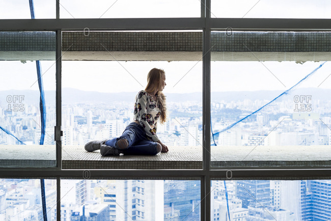 Young woman in high rise building sitting in window- looking over city
